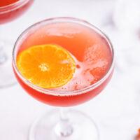 amaretto cranberry kiss cocktail with orange garnish