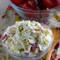 apple cole slaw in a bowl and apples in another bowl. wooden spoon on the side. set on a floral napkin