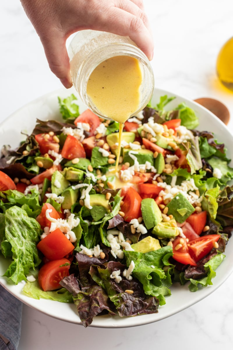 dressing being poured on salad