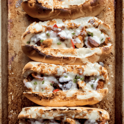 four chicken and sausage hoagies on a baking sheet