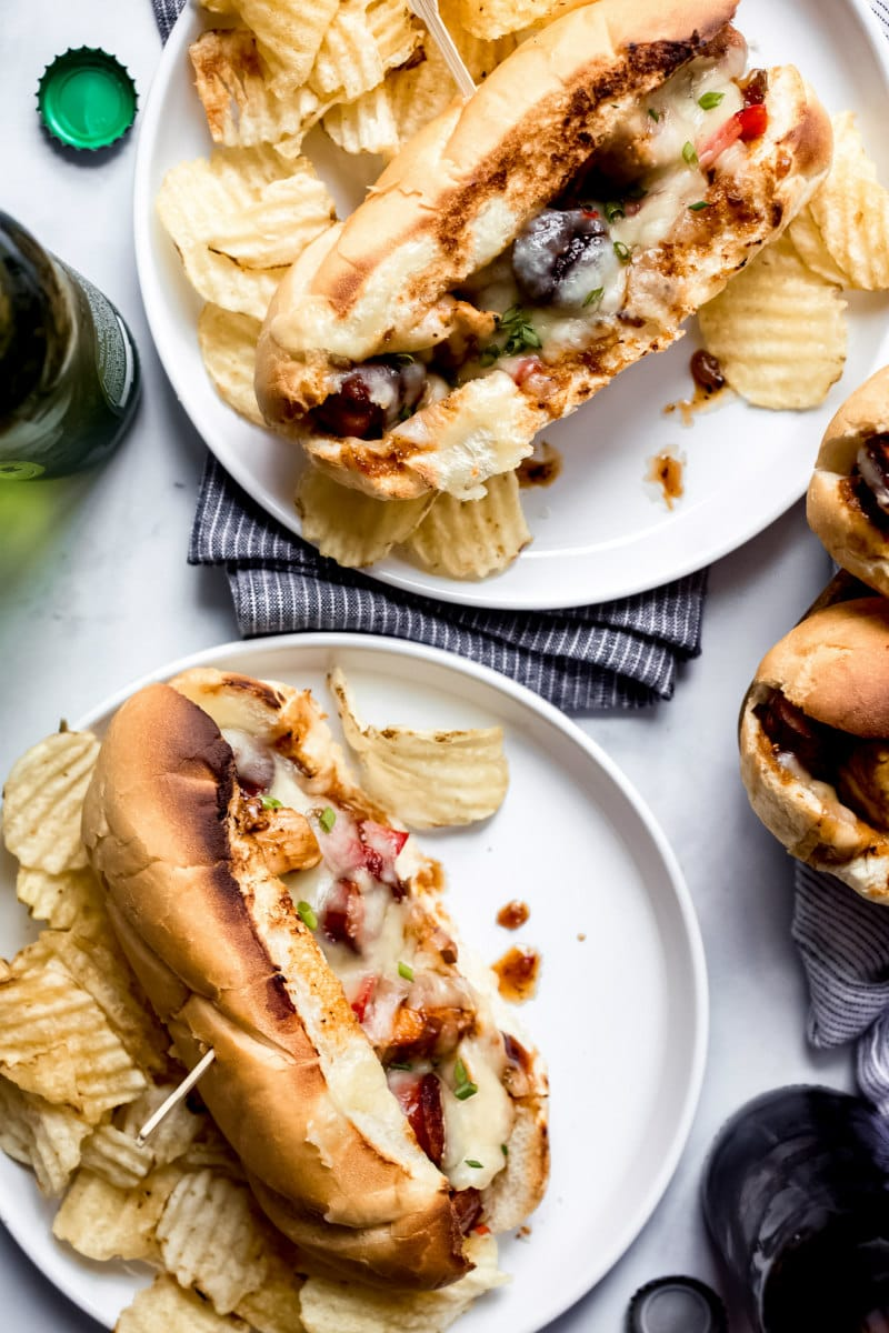 two white plates with chicken and sausage hoagies on them, served with potato chips