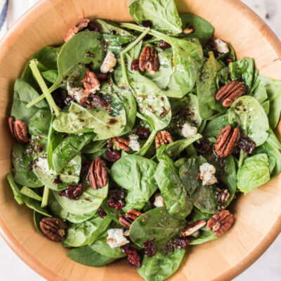 cranberry spinach salad in wood bowl