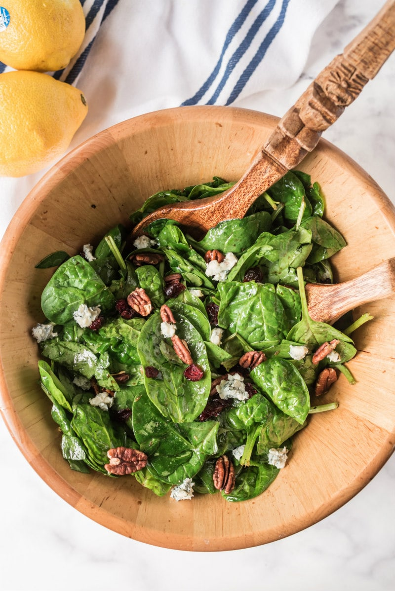 cranberry spinach salad in wooden bowl with salad servers