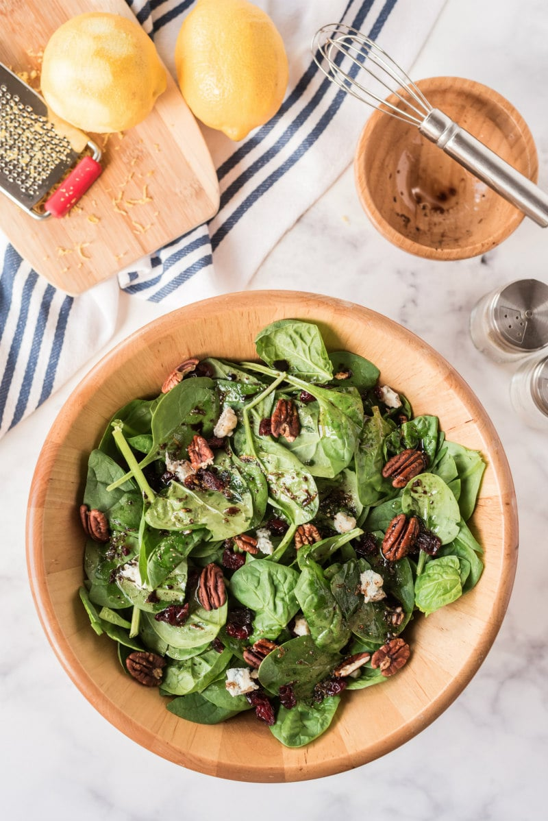 cranberry spinach salad in wooden bowl
