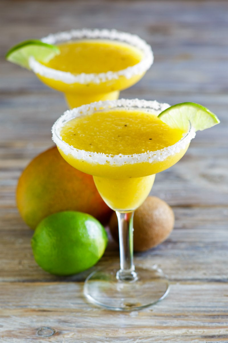 tropical margaritas in margarita glasses with lime wedge and fresh fruit displayed