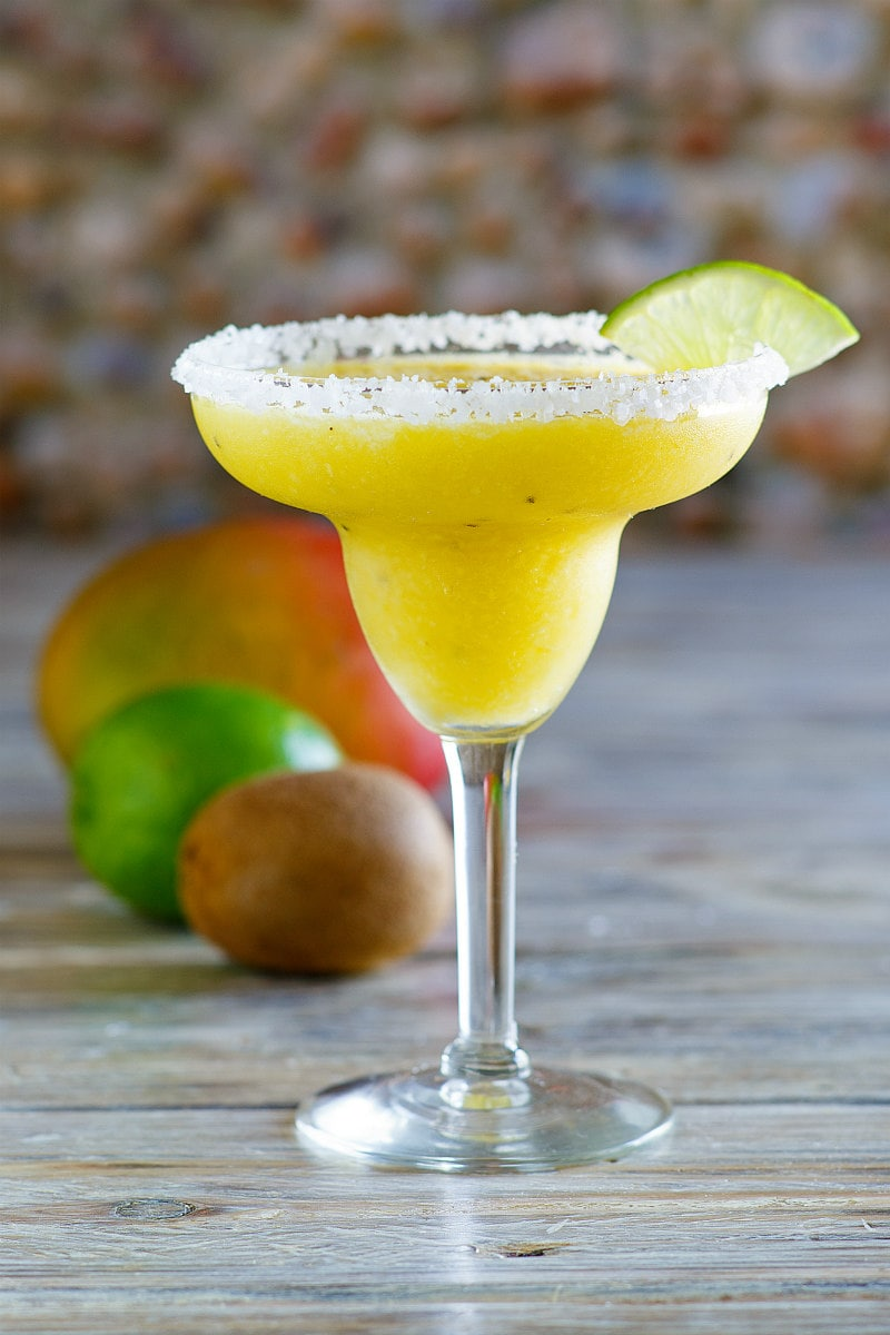 tropical margarita in a margarita glass with lime wedge and fresh fruit sitting behind
