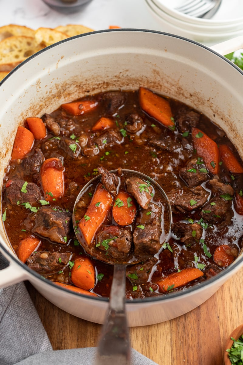 ladling out beef stew from pot