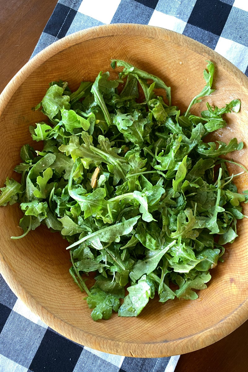 arugula tossed with dressing in wood bowl