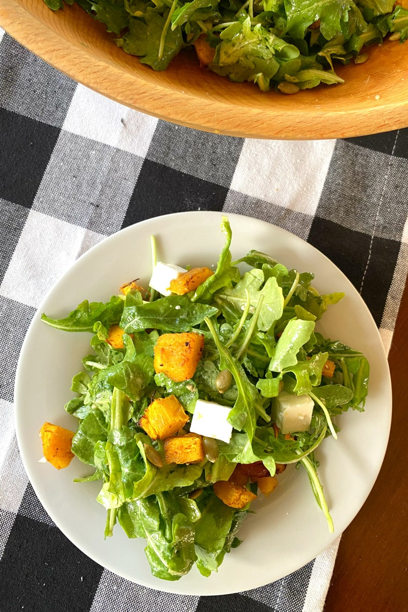 serving of maple roasted pumpkin salad on white plate