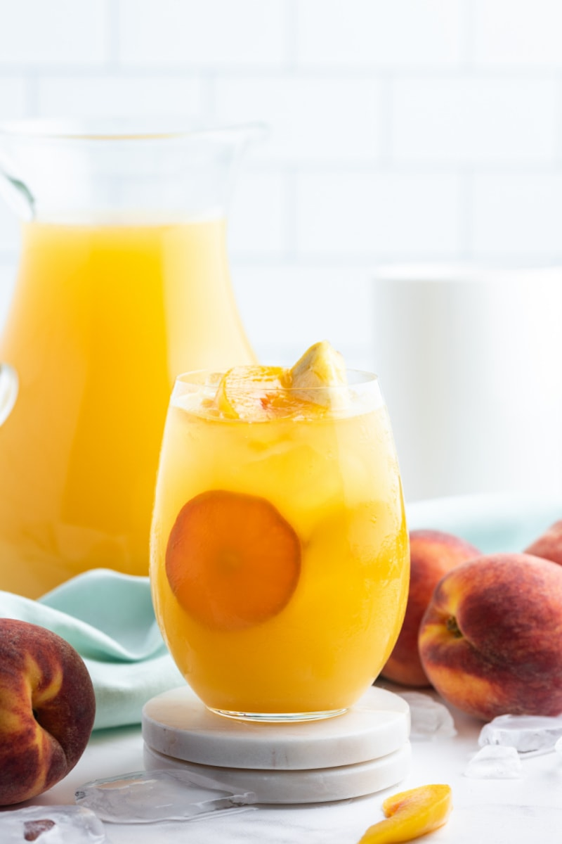 peach sangria in a glass with pitcher in background
