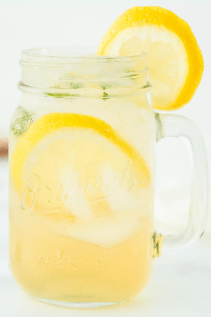vodka lemonade in a jar mug garnished with lemon