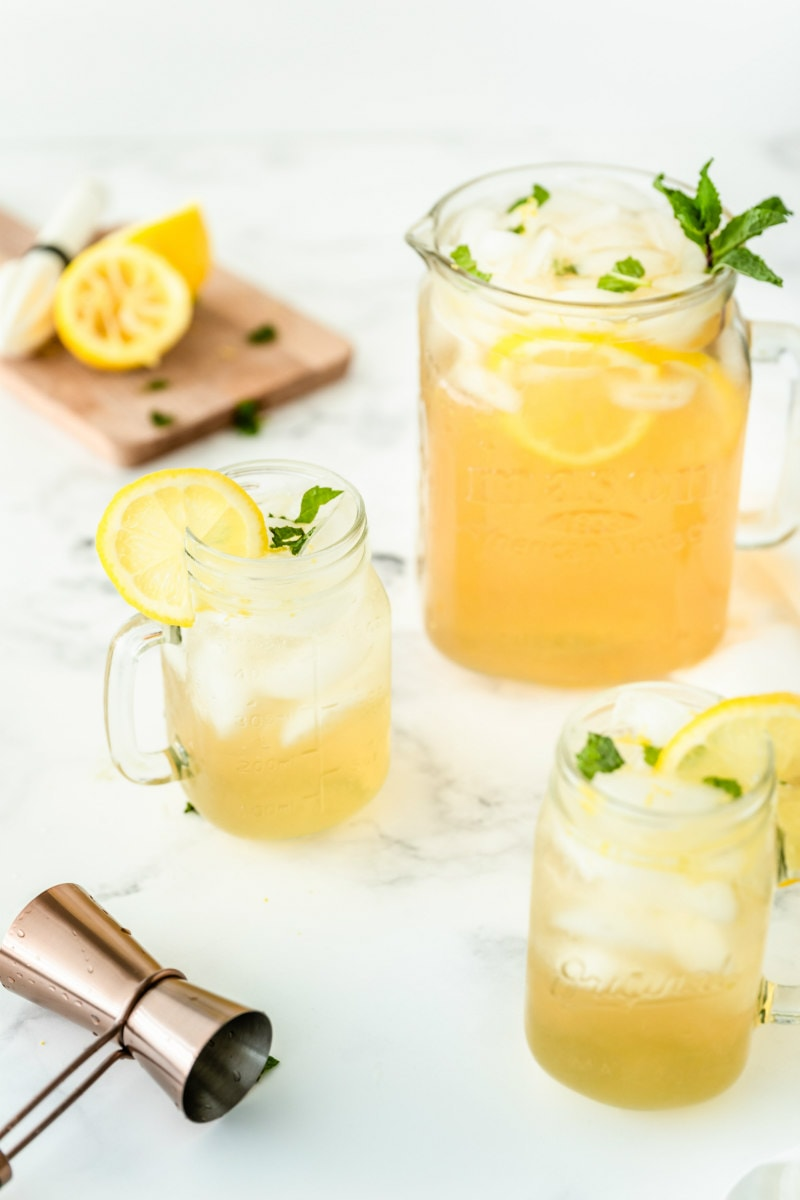 vodka lemonade in a pitcher with two servings in glass mugs. squeezed lemons in background