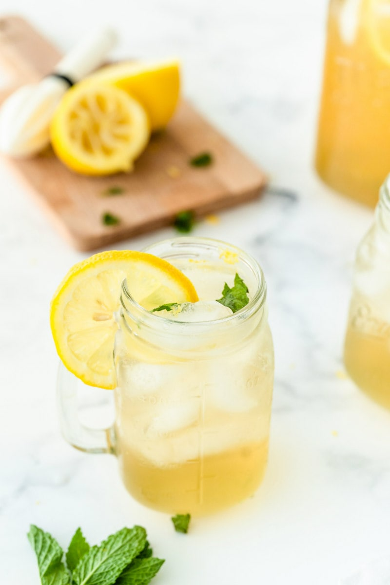 vodka lemonade in a glass mug garnished with lemon. squeezed lemons and fresh mint in background