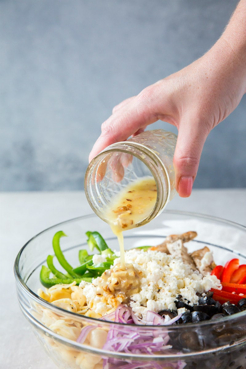 Adding dressing to Greek Tortellini Salad