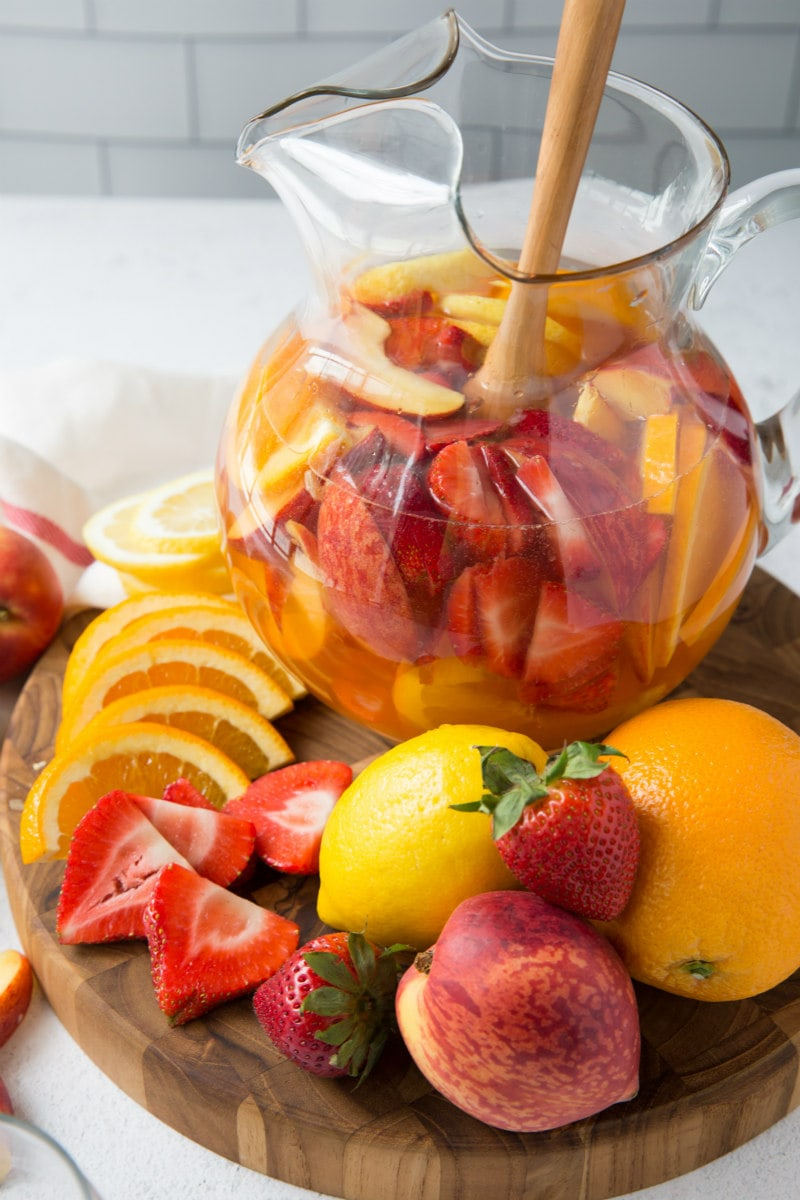 fruit platter with a pitcher of strawberry peach sangria