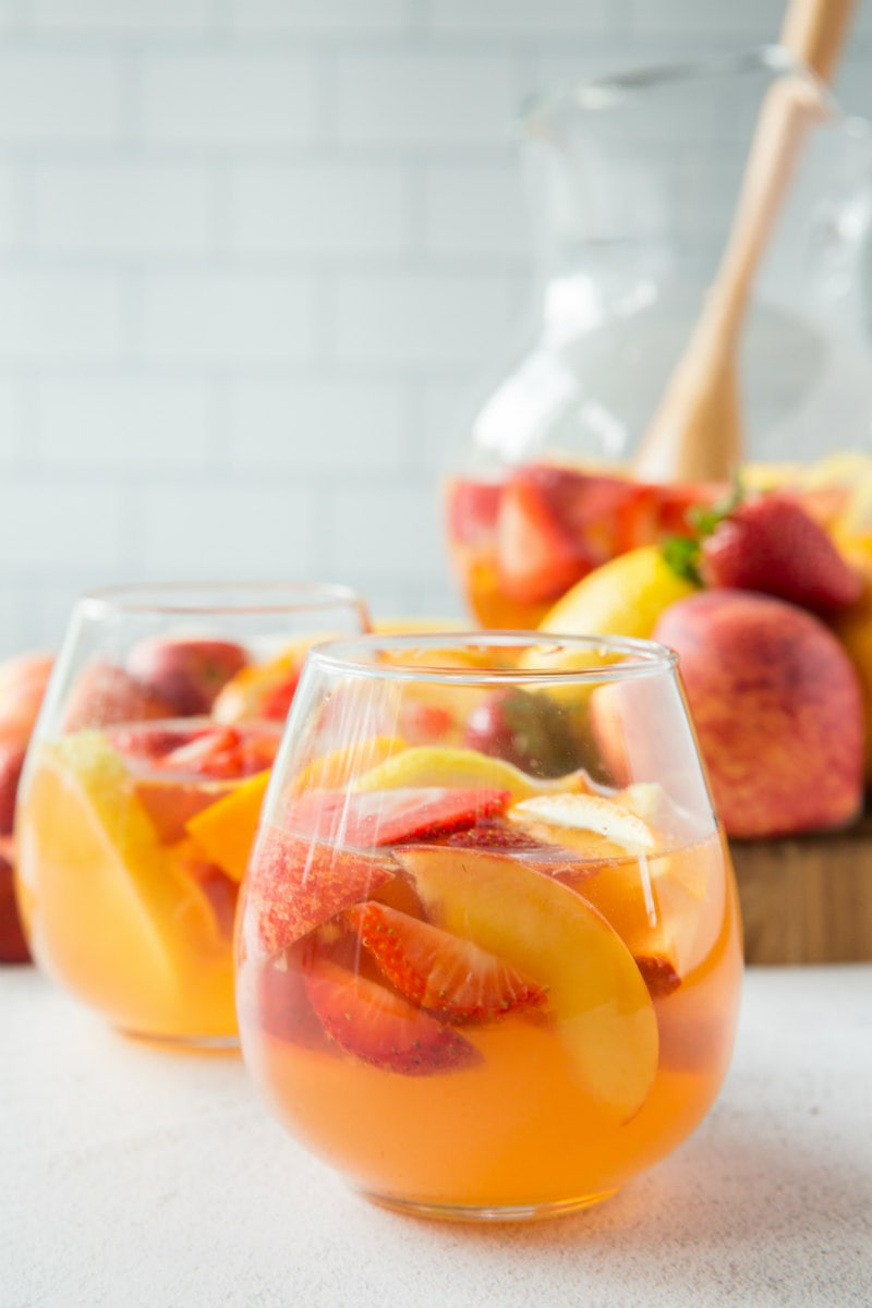 glasses of strawberry peach sangria with pitcher in background