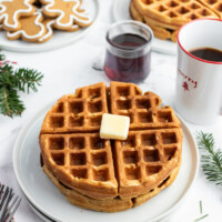 gingerbread waffles on white plate with butter