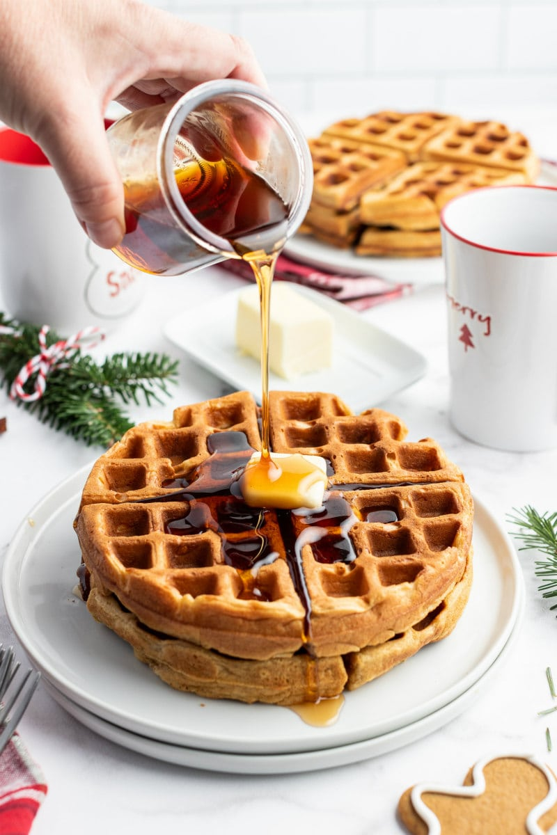 hand pouring syrup on to gingerbread waffles