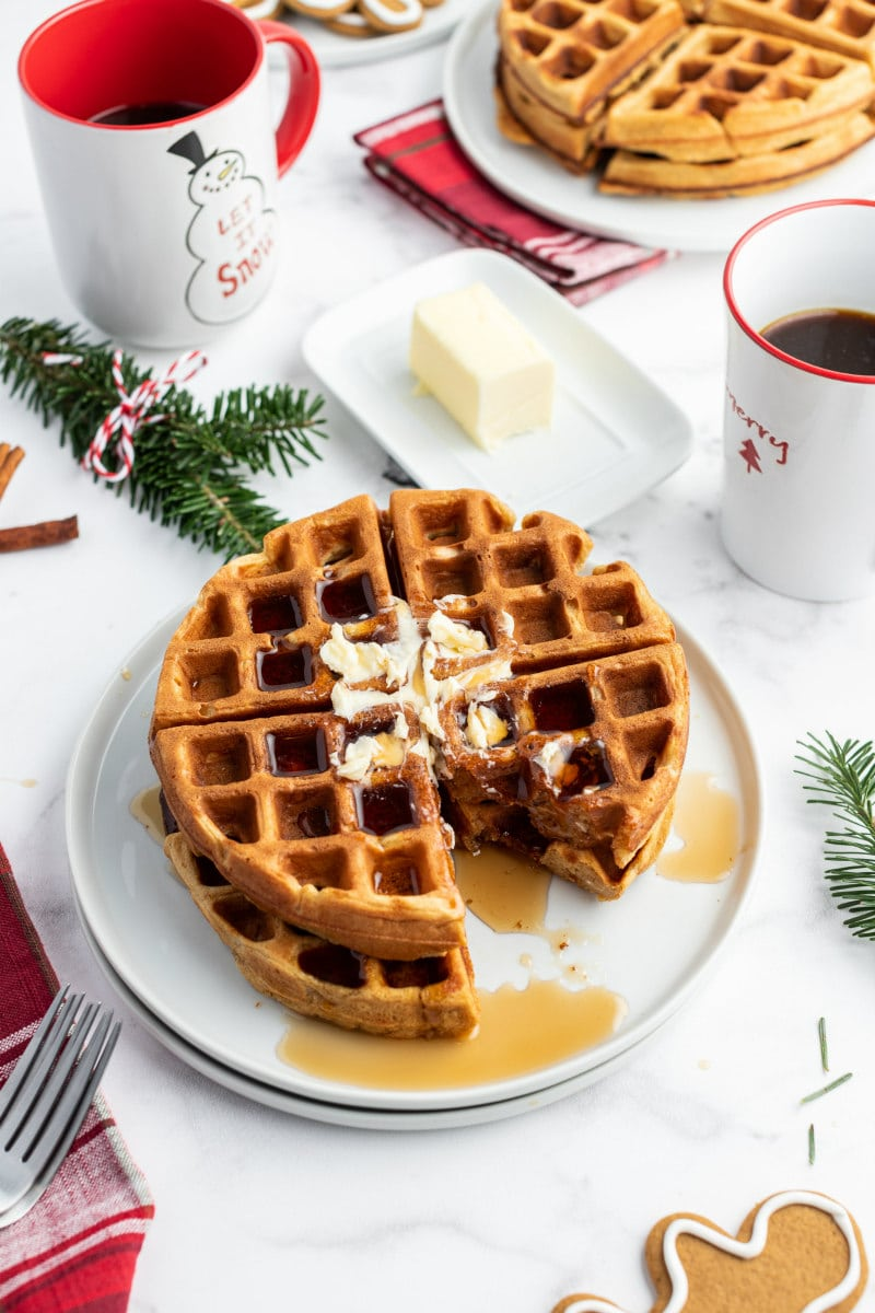 gingerbread waffles on white plate with butter and syrup