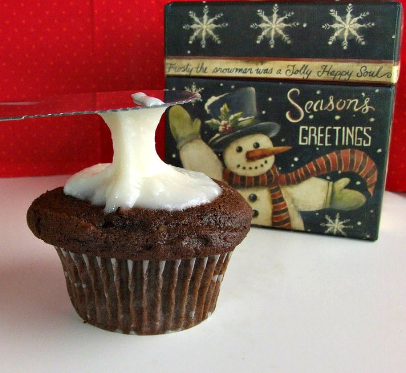 adding peppermint icing to chocolate cupcake