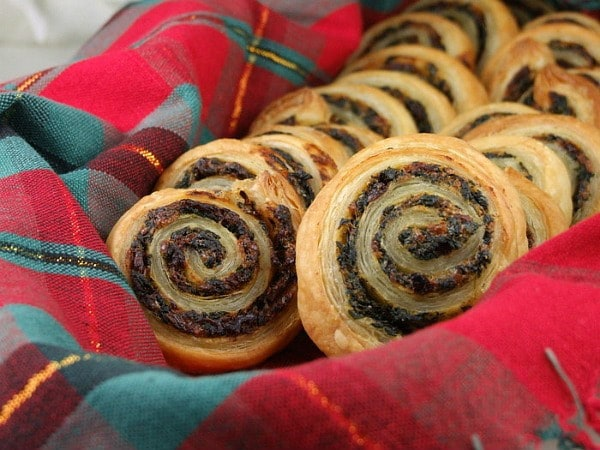 spinach and sundried tomato puff pastries in plaid napkin lined basket