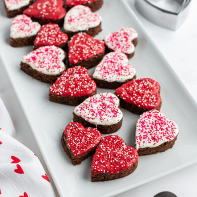 chocolate dipped brownies shaped as hearts on a white platter