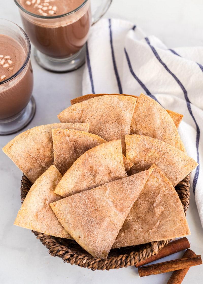 cinnamon bunuelos in a basket with hot chocolate