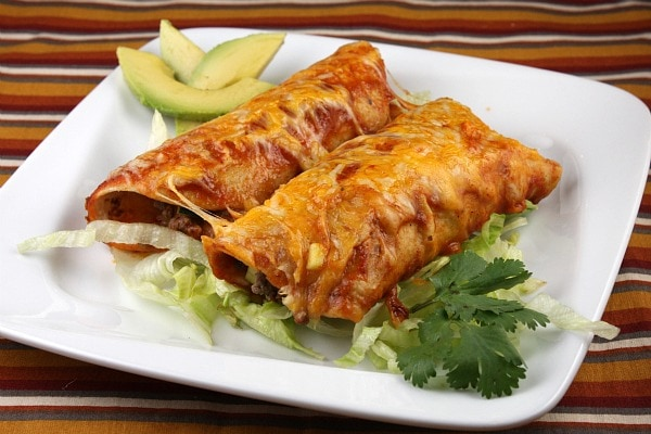 two beef enchiladas on a white plate with avocado and cilantro garnish - on a striped placemat