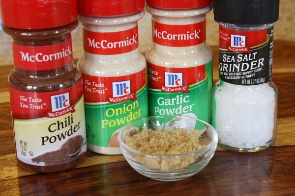 seasonings displayed for pork chop recipe: chili powder onion powder garlic powder salt and brown sugar