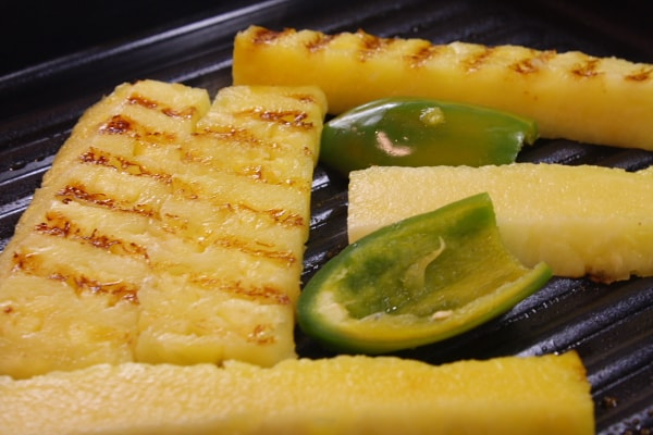 grilling pineapple and jalapeno on a stovetop grill