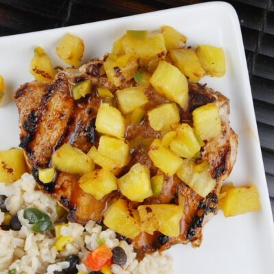 overhead shot of chili rubbed pork chops with pineapple and rice on a white plate