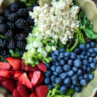 overhead shot of ingredients for triple berry salad set in a green bowl on a wooden surface