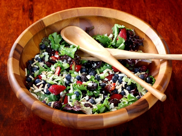 Triple Berry Salad in a large wooden bowl with wooden serving spoons