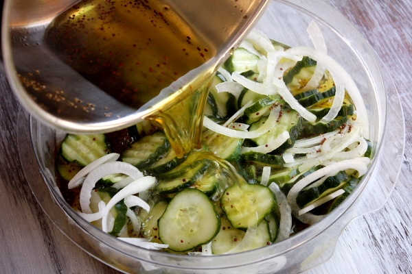 pouring pickling mixture into a glass bowl of bread and butter pickles