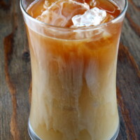 tall glass of iced coffee sitting on a wooden board