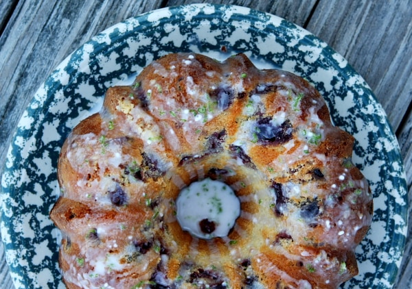 overhead shot of Cherry Limeade Pound Cake from a bundt pan displayed on a blue and white patterned cake platter