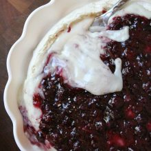 overhead shot of baked brie with blueberry sauce in a scalloped white pie dish