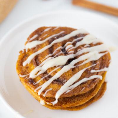 pumpkin cinnamon roll pancakes on plate with cream cheese glaze on top