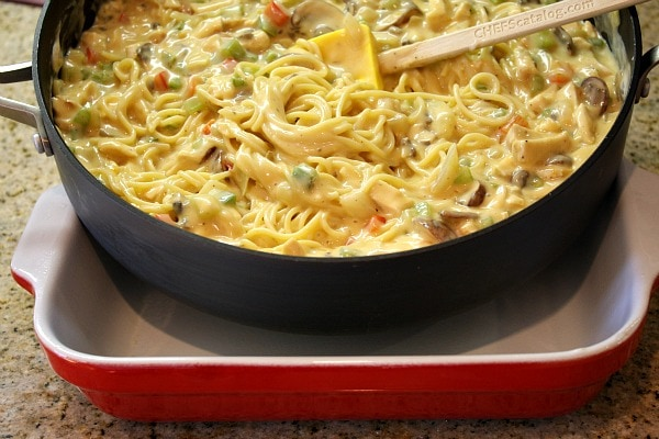 making chicken spaghetti casserole in a skillet, ready to pour it into a red and white casserole dish