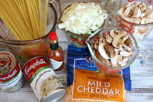 ingredients displayed for chicken spaghetti casserole- pasta, cream of mushroom soup, tabasco, cheese, onions, mushrooms, chicken