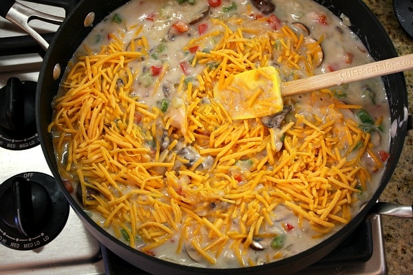 adding cheese to the sauce for chicken spaghetti casserole in a skillet