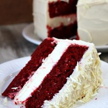 slice of red velvet cheesecake cake on a white plate with the cake in the background