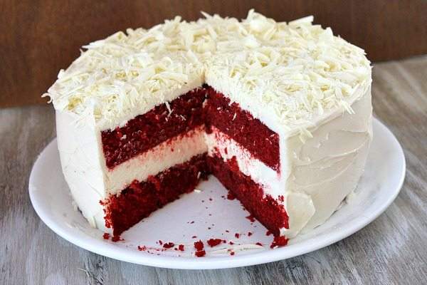 red velvet cheesecake cake on a white plate sliced open to see the inside
