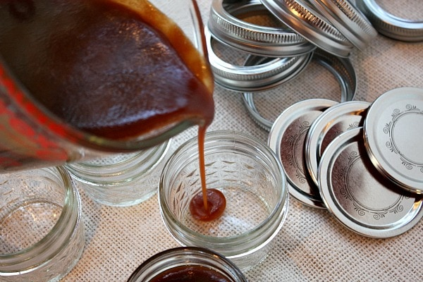 pouring salted caramel sauce into jars