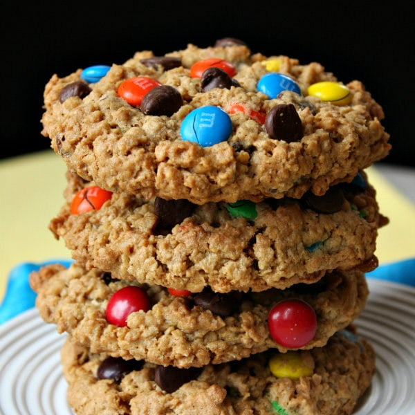 stack of monster cookies on a white plate with a yellow and black background