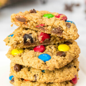 stack of monster cookies with the cookie on top split in half to show the inside