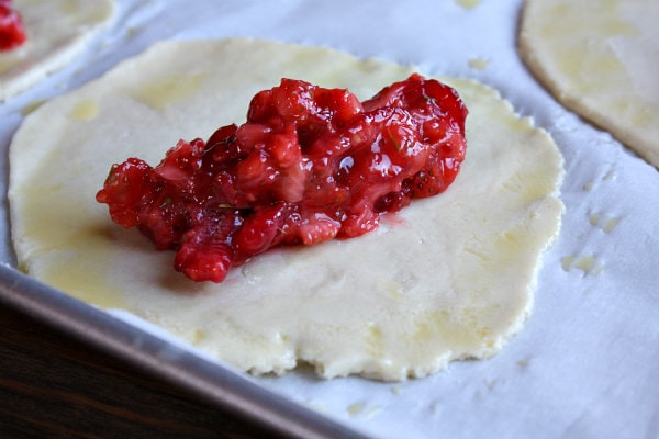Berry Hand Pie dough on a baking sheet with berries in the middle of the rolled out round of dough