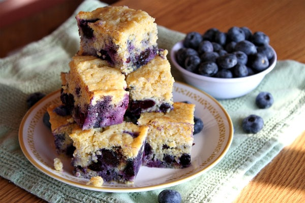stack of slices of blueberry cornbread on a plate set on a green napkin. bowl of blueberries in white bowl on the side