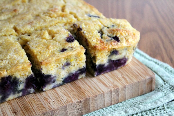 blueberry cornbread cut into pieces on a cutting board set on a green cloth napkin