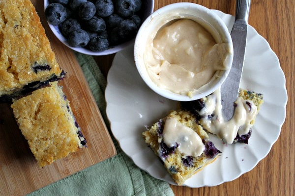 overhead shot of blueberry cornbread on a cutting board with a bowl of fresh blueberries and a slice of cornbread on a white plate with butter on it and a bowl of butter and a knife